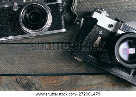 Old retro cameras on rustic wooden planks background - stock photo