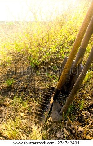 Old retro garden tools (cultivator, shovel, rake) over brown soil close up, vertical.  Agriculture, gardening, soil cultivation, village life concept. - stock photo
