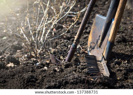 Old retro garden tools (cultivator, shovel, rake) over brown soil (ploughed land) close up.  Agriculture, gardening, soil cultivation, village life concept. - stock photo
