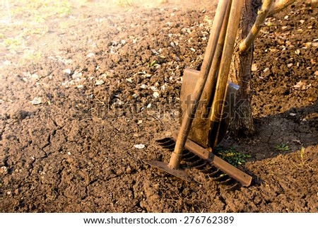 Old retro garden tools (cultivator, shovel, rake) over brown soil (ploughed land) close up, horizontal.  Agriculture, gardening, soil cultivation, village life concept. - stock photo