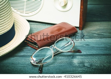 Old retro glasses, radio and a hat on a wooden table. Toned photo. - stock photo