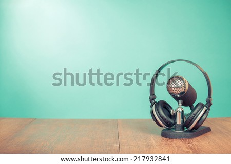 Old retro microphone and headphones on table front mint green background - stock photo