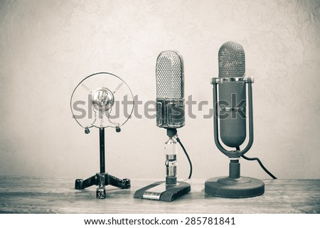 Old retro microphones from 50s on table. Vintage style sepia photo - stock photo