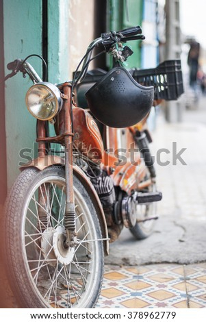 Old retro motorcycle with helmet parked on a little street of Morocco - stock photo