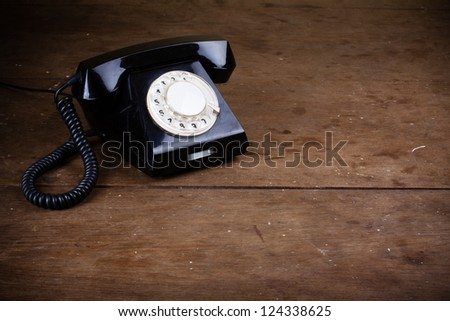 Old retro phone with rotary disc on wooden table grunge background - stock photo