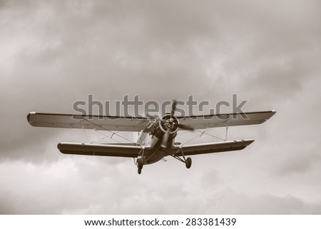 Old retro plane flies in the sky. - stock photo