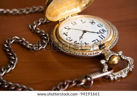 Old retro pocket watch with chain on table - stock photo