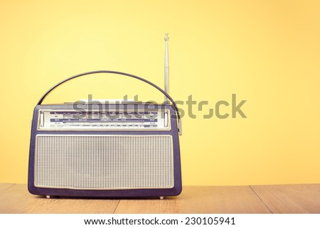 Old retro portable radio front yellow background - stock photo
