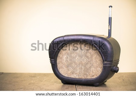 Old retro radio receiver on wood table - stock photo
