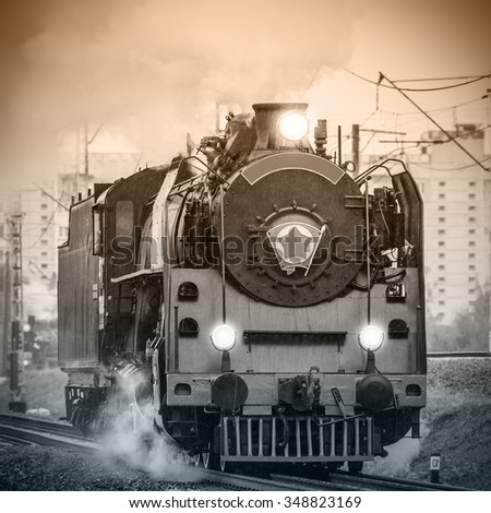 Old retro russian steam locomotive under the pouring rain. - stock photo