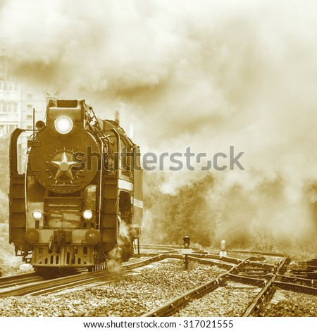 Old retro steam locomotive moves under the pouring rain. - stock photo