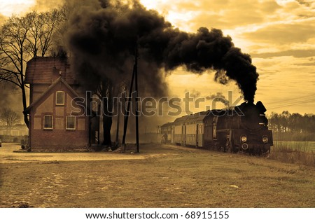 Old retro steam train stopped at the small station - stock photo