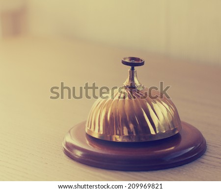 Old retro style hotel bell on a wood stand. Copy space - stock photo