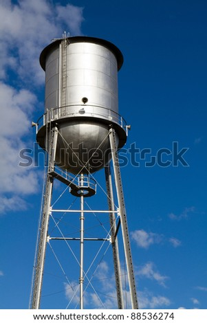 Old retro style water tower that has been restored and painted against a blue sky. Sirens are attached and used as a community alert system.