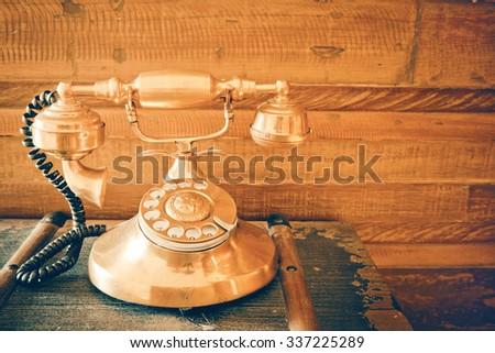 Old retro telephone on wooden box - stock photo