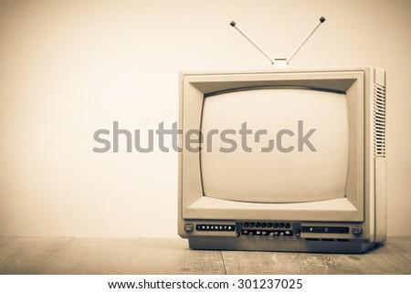 Old retro television on table. Vintage style sepia photo - stock photo