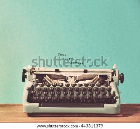 Old retro typewriter on table on blue background - stock photo