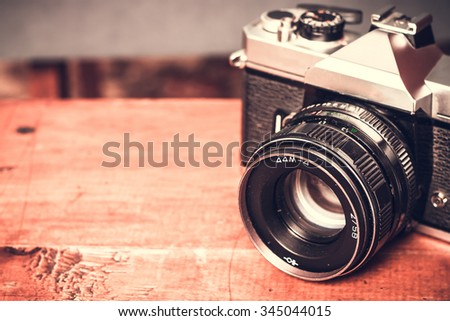 Old retro vintage camera photography. Antique lens equipment. Black object film photo. Classic creative background. Table image. Obsolete nostalgia style.  - stock photo