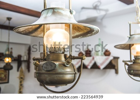 Old retro vintage metallic decorative lamp with patina hanging on the ceiling of a russian tavern interior. Rustic style electric lamp imitated antique rustic kerosene lamp  - stock photo
