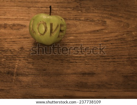 Old retro vintage style aged texture brown wooden table Background of green apple cut into letter in word love valentines day fruit dessert  photo romance Empty copy space for inscription - stock photo