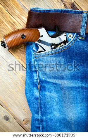 old revolver in the pocket of vintage blue jeans - stock photo