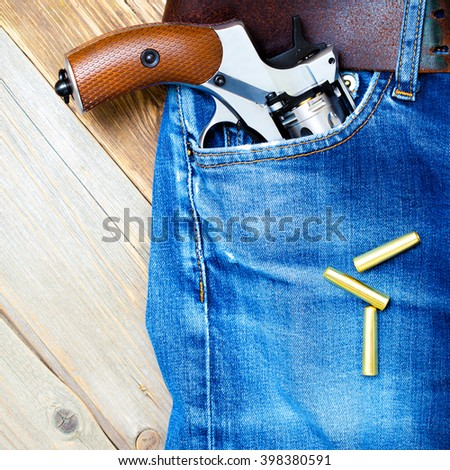 old revolver nagant with brown handle in the pocket of vintage blue jeans, close up - stock photo