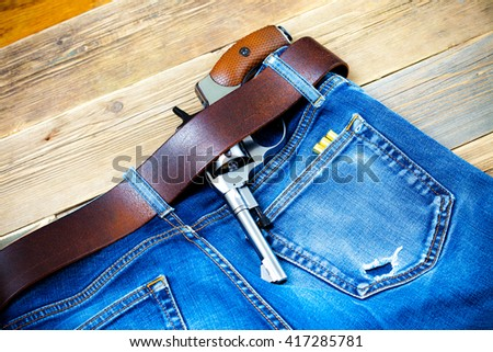old revolver tucked behind a leather belt of old blue jeans and several rounds of ammunition in his pocket - stock photo