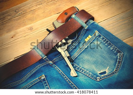 old revolver tucked behind a leather belt of old blue jeans and several rounds of ammunition in his pocket. instagram image filter retro style - stock photo