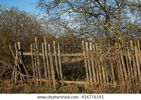 Old rickety fence in the countryside - stock photo
