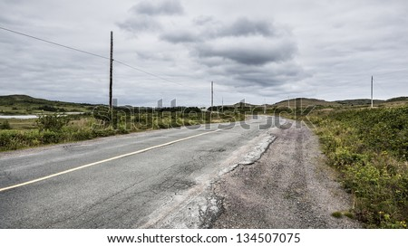 Old Road Fades into the Horizon Underneath a Dark Cloud Formation: A rural road with cracked pavement leads to the horizon.  Greenery runs alongside the road and a dark cloud formation hangs over it.