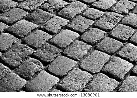 Old road made of stones in bw - stock photo