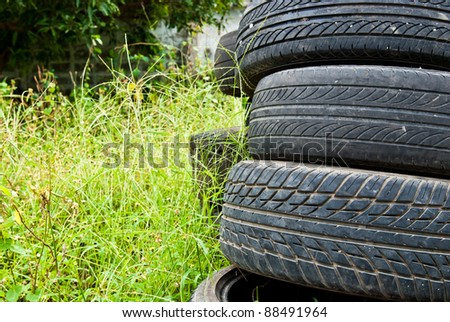 Old road tires stacked on grass land as background - stock photo