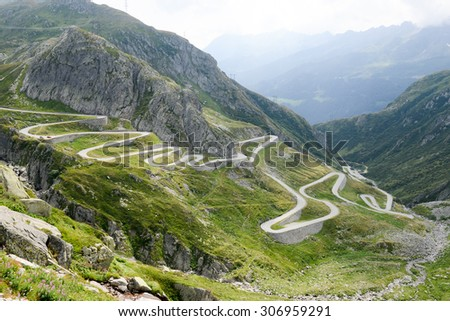 Old road with tight serpentines on the southern side of the St. Gotthard pass bridging swiss alps - stock photo