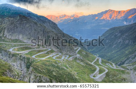 Old road with tight serpentines on the southern side of the St. Gotthard pass bridging swiss alps at sunset - stock photo