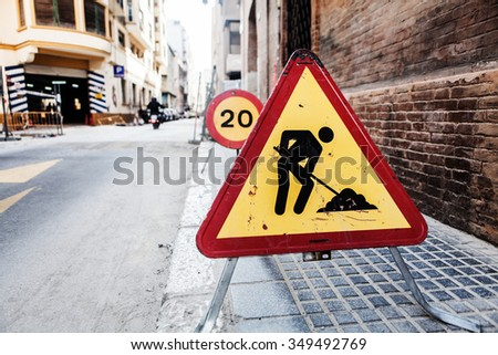 Old road works sign. Grunge style. Old condition. Road sign of work in progress against on the sidewalk. - stock photo