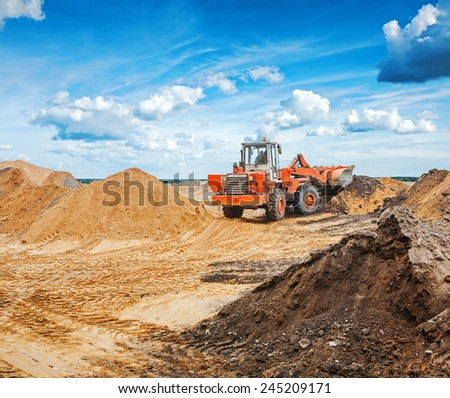 old roadworking tractor working with construction sand - stock photo