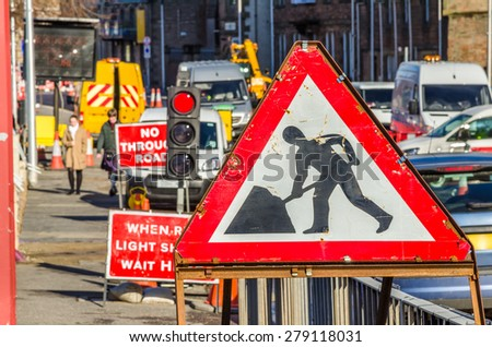 Old Roadworks Sign on a Busy Road in Scotland - stock photo