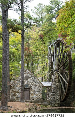 Old rock water mill hiding in the trees - stock photo
