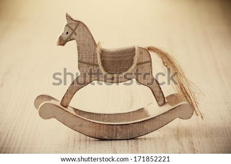 Old rocking horse on a rustic country backdrop. - stock photo