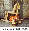 Old rocking horse  with orange lilies and daisies in an antique copper vase on a rustic wood backdrop. - stock photo
