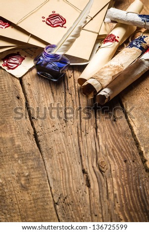 Old rolls of paper and blue ink in the inkwell as vintage background - stock photo