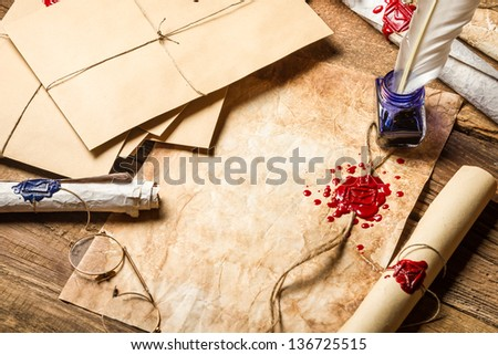 Old rolls of paper, glasses and blue ink in the inkwell - stock photo