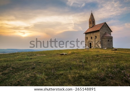 Old Roman Catholic Church of St. Michael the Archangel on the Hill at Sunset in Drazovce, Slovakia - stock photo