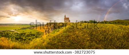 Old Roman Catholic Church of St. Michael the Archangel with Rainbow on the Hill at Sunset in Drazovce, Slovakia - stock photo