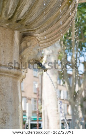 Old Roman fountain in French village - stock photo