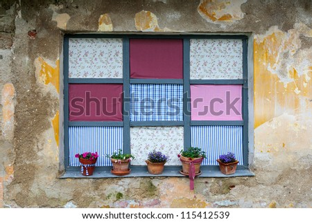 Old romantic windows with flowerpots and printed fabric - stock photo