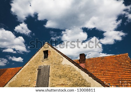 Old roof on a blue cloudy Sky - stock photo
