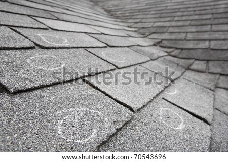 Old roof with hail damage, chalk circles mark the damage. Shallow depth of field - stock photo
