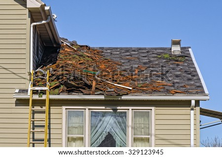 Old Roofing Being Removed on House to be Replaced by New Shingles - stock photo