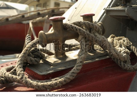 Old rope on the bow of old motorboat. - stock photo